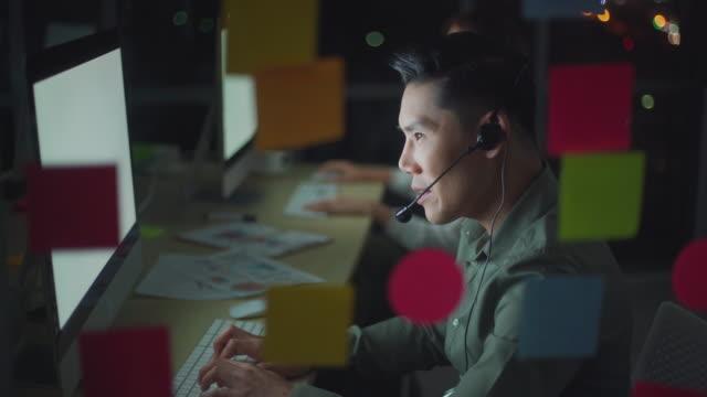 オフィスで新しいビジネスを開始するために遅くまで働くコンピュータとヘッドセットを使用してアジアのビジネスマン - ヘッドセット点の映像素材/bロール