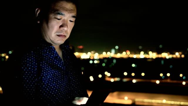Homme d'affaires asiatiques à l'aide de Smartphone dans la ville pendant la nuit