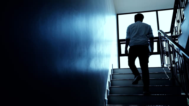 asian business man walking up the stairs in office - steps and staircases stock videos & royalty-free footage