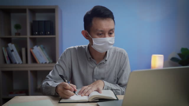 asian business man wearing protective face mask writing on notebook working late night at office - chinese ethnicity stock videos & royalty-free footage