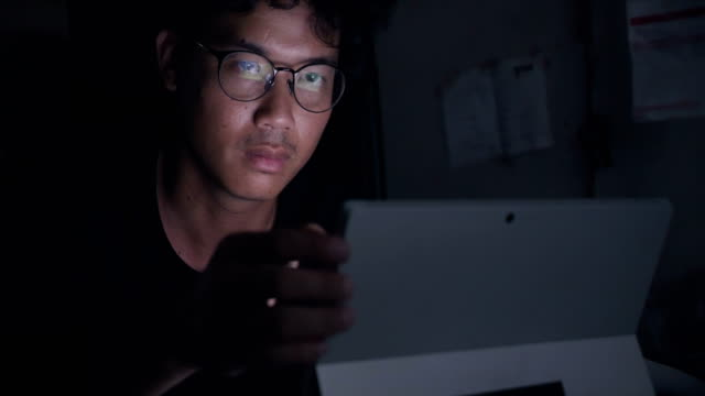 Asian business man working late with laptop and smart phone.