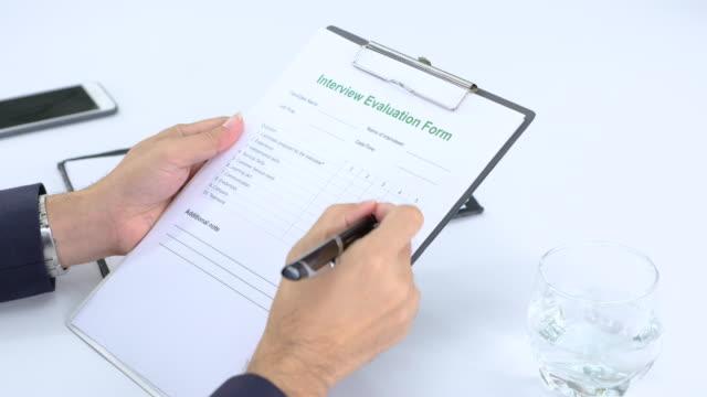 vidéos et rushes de formulaire d'évaluation de cocher affaires asiatiques gestionnaire du demandeur et panoramique à interviwer face à atteindre room.job entrevue - recrue