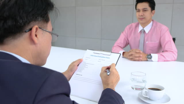 asian business manager check interview evaluation form of applicant resume in meeting room.job interview. - wages stock videos & royalty-free footage