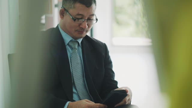 Asian business manager is using smart phone with positive emotion