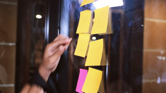 asian business men and women smiling and working together on wall glass with post it stickers. modern startup office - answering stock videos & royalty-free footage
