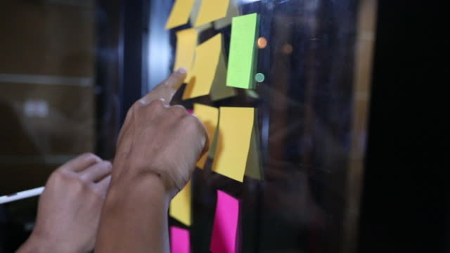 vídeos de stock e filmes b-roll de asian business men and women smiling and working together on wall glass with post it stickers. modern startup office - nota mensagem