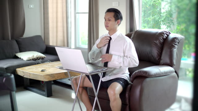 asian business men wear white shirt with necktie and short pant sitting on sofa using laptop for video conference in the living room at home - camicia video stock e b–roll