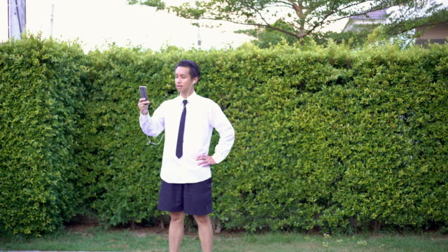 vídeos de stock e filmes b-roll de asian business men wear white shirt with necktie and short pant using a smartphone for video conference in the garden at home - formal garden