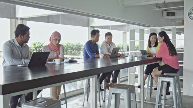Asian business people working at long table in office