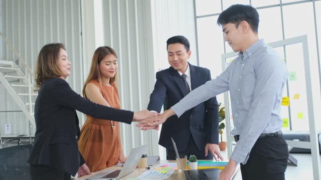 vidéos et rushes de équipe d'affaires asiatique mettant leurs mains ensemble les uns sur les autres dans le bureau. groupe de gens d'affaires d'asie joignant des mains affichant le travail d'équipe d'unité - col blanc