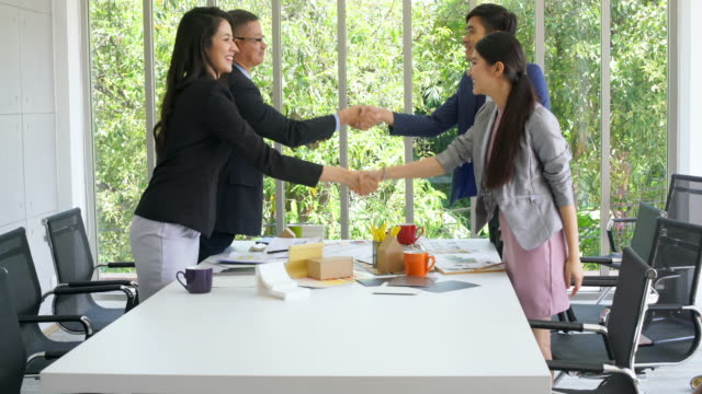 Asian Business Team Shaking Hand In Meeting