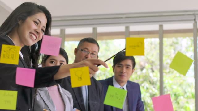 vidéos et rushes de affaires asiatiques équipe part idée sur une planche en plastique - planche de bois