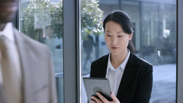 asian business woman having a video call while standing in the hallway of a modern business building - part of a series stock videos & royalty-free footage