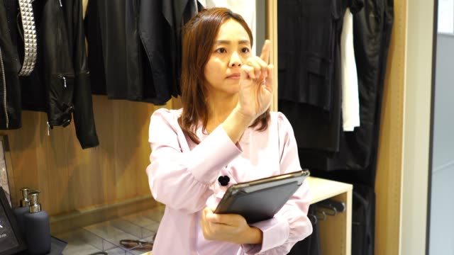 asian business woman in store checking inventory on digital tablet ,index finger pointing and hand slide in the air - index finger stock videos & royalty-free footage