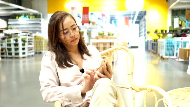 vídeos de stock, filmes e b-roll de mulher de negócios asiáticos em armazenar inventário verificação em smartphone - agenda eletrônica