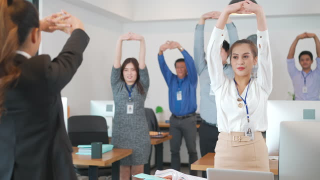 asian business woman leading business people team exercise for a few minutes of rigorous bending, stretching and thrusting as part of a regular calisthenics drill in office in morning. - healthy lifestyle stock videos & royalty-free footage