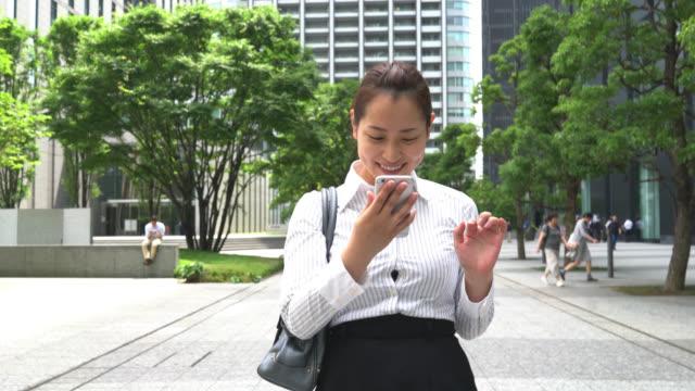 Asian business woman looking at her smartphone enjoying social media gossip