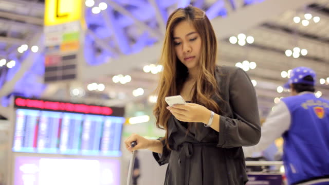 asian business woman on smart phone at airport - 2015 stock videos & royalty-free footage
