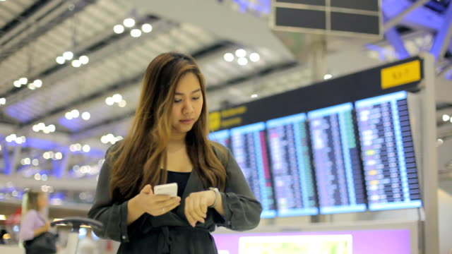 Mulher de negócios asiáticos no telefone inteligente no aeroporto