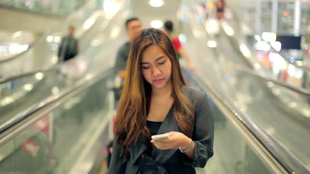 Asiatische Geschäftsfrau auf Smartphone am Tor warten im terminal Flughafen