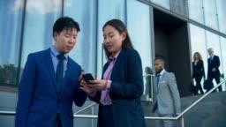DS Asian business woman showing her male colleague the data on her phone and asking for advice in front of the business building