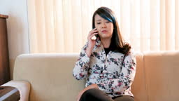 Asian business woman solving problems using cell phone
