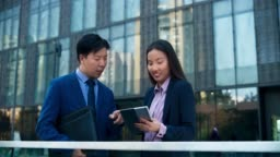DS Asian business woman talking to her Asian male colleague while scrolling the tablet in front of the business building