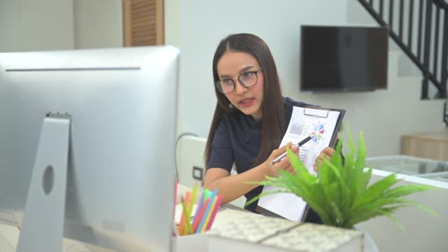 asiatisk affärskvinna pratar med sina kollegor om plan i videokonferens. multietniskt affärsteam använder dator för ett onlinemöte i videosamtal. grupp av människor smart arbetar hemifrån. - intervju evenemang bildbanksvideor och videomaterial från bakom kulisserna