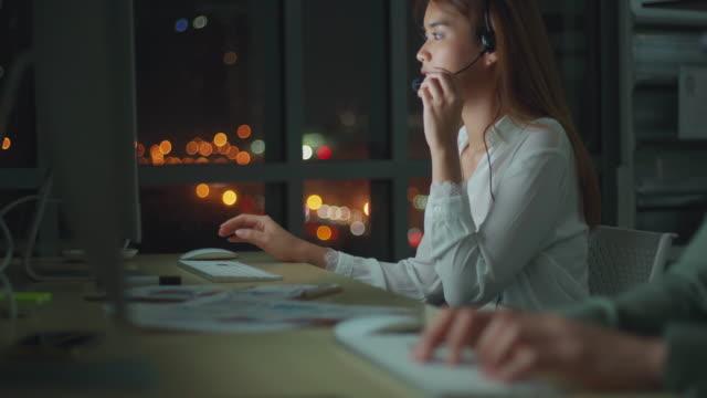 asiatisk affärskvinna som använder dator och headset arbetar sent för att starta nya affärer på kontoret - jobba över bildbanksvideor och videomaterial från bakom kulisserna