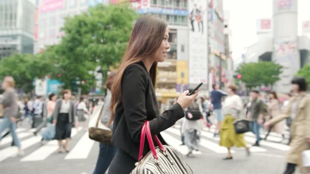 asian business woman walking across a crowded crosswalk while scrolling on her mobile phone in tokyo, japan - brown hair stock videos & royalty-free footage
