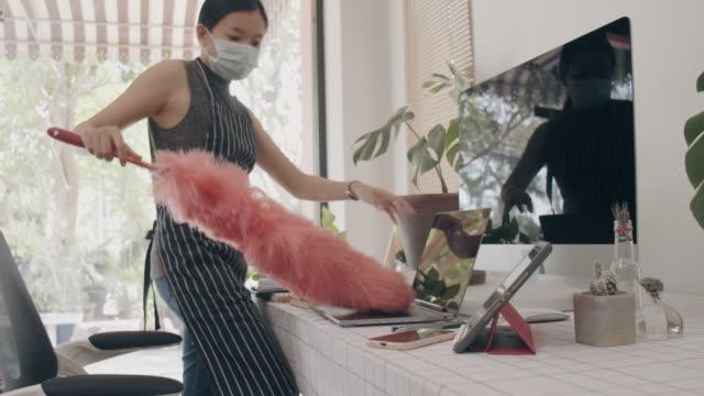 stockvideo's en b-roll-footage met aziatische bedrijfsvrouw die beschermend masker draagt en van huis met het schoonmaken tablet en computer op lijst met veerduster werkt. concept van sociale distantiëring is infectie bestrijding actie om de verspreiding van de ziekte van corona virus te s - kokerworm