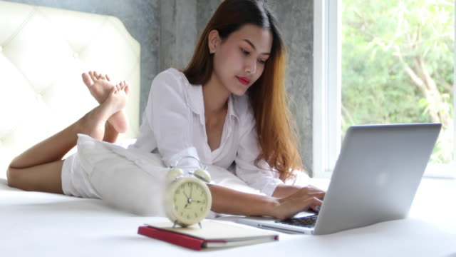 Asian business women using notebook and smiling happy for working on bed