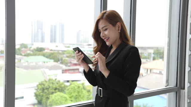 vidéos et rushes de femmes asiatiques d'affaires utilisant le sourire de smartphone et de tablette heureux pour travailler et écrire - site internet