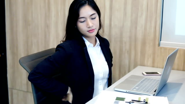 asian business women with back pain sin an office and working hard,slow motion - posture stock videos and b-roll footage