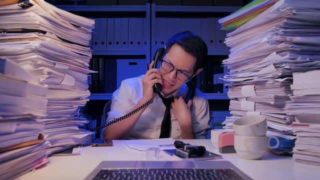 アジアの実業家32歳は、夜遅くまで働くなどで、ストレスに不満を抱く書類で忙しい眼鏡をかけた32歳。後期コンセプトを働く。 - 積み重なる点の映像素材/bロール