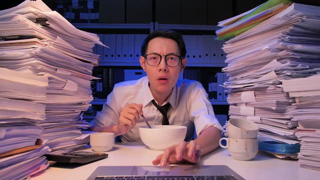 vidéos et rushes de homme d'affaires asiatique âge 32 ans portant des lunettes appréciant manger des nouilles pour le dîner tout en utilisant l'ordinateur portable avec le stress dû au travail excessif dans le bureau la nuit de travailler tard. travailler late concept - new age concept