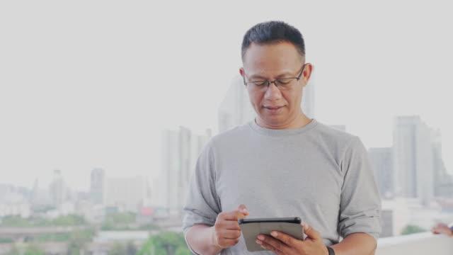 vídeos de stock, filmes e b-roll de empresário asiático de 40 a 50 anos usando roupas casuais, usando um telefone ou smartphone para conversar com clientes - ferramenta de trabalho