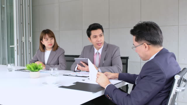 asian businessman and businesswoman try to sale product to customer and got agreement in meeting room at modern office - dealing cards stock videos and b-roll footage