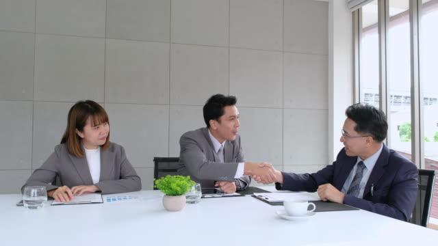 アジア系のビジネスマン、ビジネスウーマンの顧客に製品を販売しようし、会議室で近代的なオフィスの契約を得た - アジア大陸点の映像素材/bロール