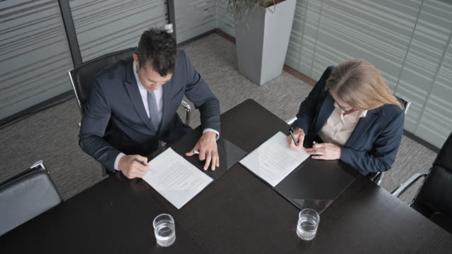 vídeos de stock e filmes b-roll de cs asian businessman and caucasian businesswoman signing a contract in the conference room and shaking hands - contrato