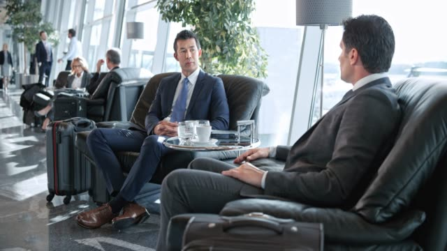ds asian businessman and his caucasian colleague talking in the business lounge at the airport - ethnicity stock videos & royalty-free footage