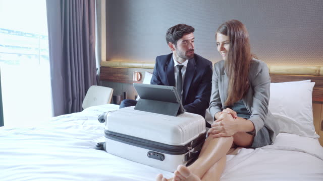 asian businessman and russian beautiful businesswoman wearing formal clothes sitting on white bed having business meeting, discussing on digital tablet laying on  wheeled luggage with positive emotion of smiling in the luxury hotel resort room. - 25 29 years stock videos & royalty-free footage