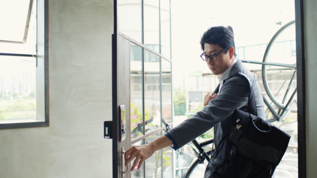 vídeos de stock e filmes b-roll de asian businessman arriving in coworking space carrying bicycle - chegada