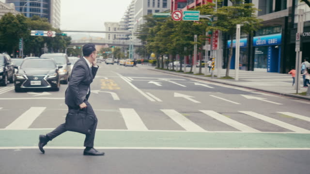 asian businessman crossing the street in a hurry and talking over the phone - necktie stock videos & royalty-free footage