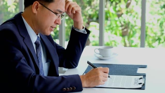 アジア系のビジネスマンのオフィス、ビジネス コンセプトで契約を読みながら気にさわる - 疑念点の映像素材/bロール