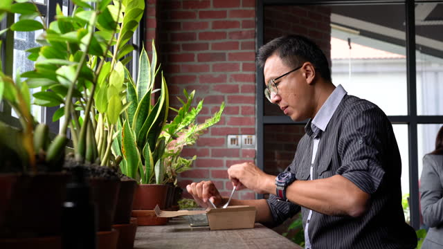 vidéos et rushes de homme d'affaires asiatique mangeant la nourriture de prise dans le bureau - un seul homme