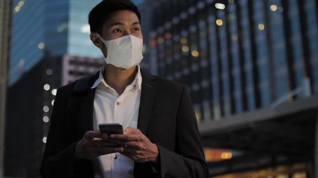 アジアのビジネスマンは、彼の携帯電話で新しい仕事を見つける - クラシファイド広告点の映像素材/bロール