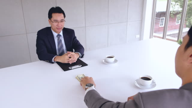 stockvideo's en b-roll-footage met aziatische zakenman hand over omkopen geld naar een ander businessman.businessman geld rekening pak en ondertekenen van een contract in onderhandeling teken vergadering van project contract. corruptie concept. - omkoping