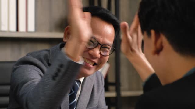vidéos et rushes de homme d'affaires asiatique haut-fiving pour le plan de succès au bureau - collègue