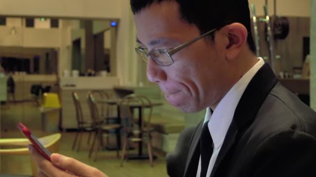 stockvideo's en b-roll-footage met aziatische zakenman die slimme telefoon bij café speelt - leesbril